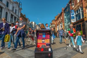 A brightly coloured arcade game with a joystick in the middle of a busy street