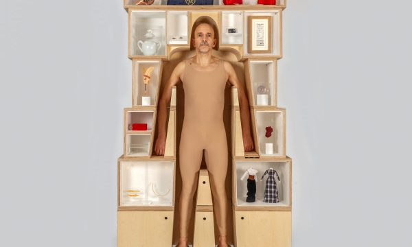 A man stood inside a wearable museum, surrounded by display cases built around his body and above his head.