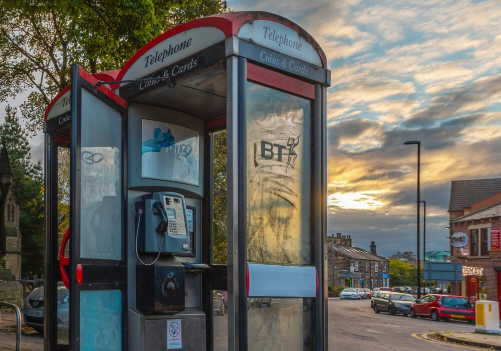 A phone-box with light graffiti in front of a sunset.