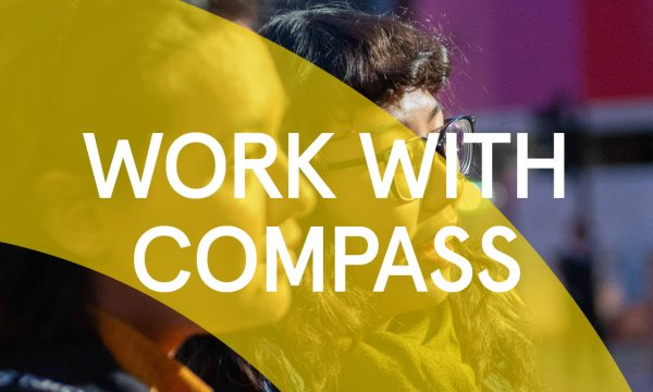 """Close up of the faces of two people, both white who are looking to the right. They are audience members of a Compass Festival Event. There is a Yellow arch graphic that goes across the image, what text that says """"work with compass"""" is written across the whole image."""